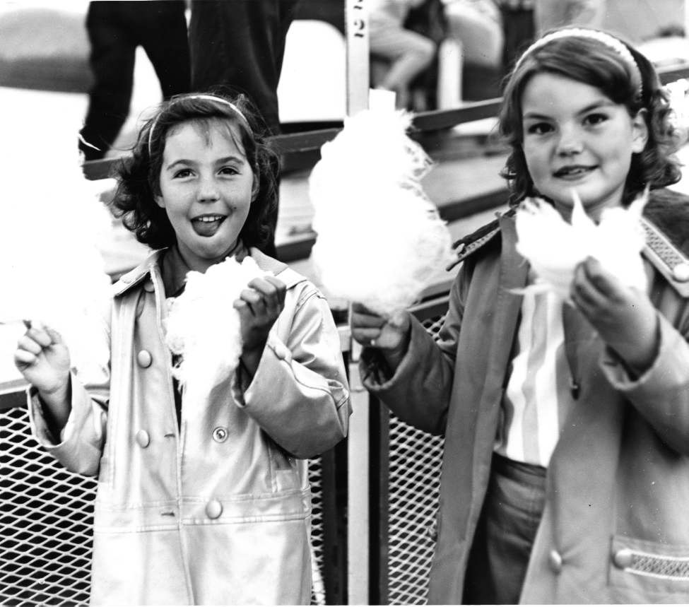 Linda Jackin, 9, and Nancy Flavell, 9, enjoy treats at the Red River Exhibition parade, July 3, 1961.