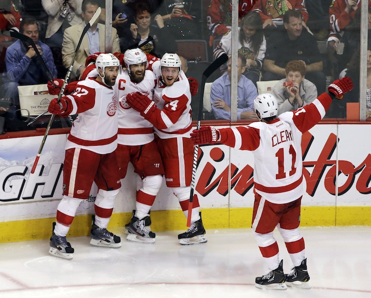 Detroit Red Wings center Henrik Zetterberg (second from left) celebrates with Kyle Quincey (27), Gustav Nyquist (14) and Daniel Cleary (11) after evening the score 1-1 early in the third period.  (Nam Y. Huh / The Associated Press)