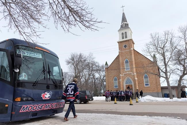 Regina Pat Canadians player Jared Thompson crosses the street to join his teammates before the funeral for Adam Herold at Sacred Heart Church in Montmartre, Sask., on Friday April 13, 2018. The 16-year-old Humboldt Broncos hockey player was killed in a bus crash on April 6 near Tisdale. THE CANADIAN PRESS/Michael Bell