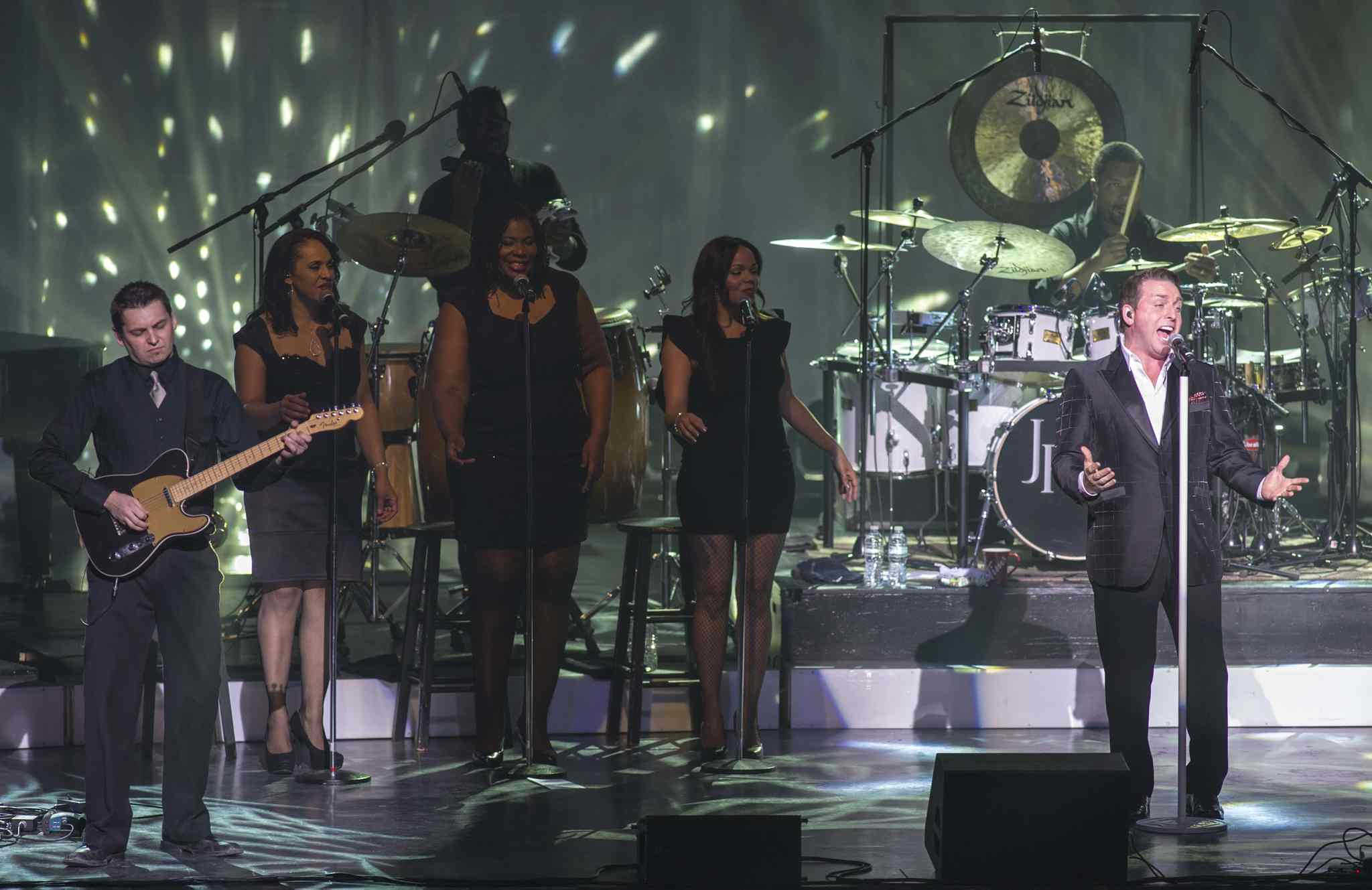 Backup singers and band perform with Johnny Reid.