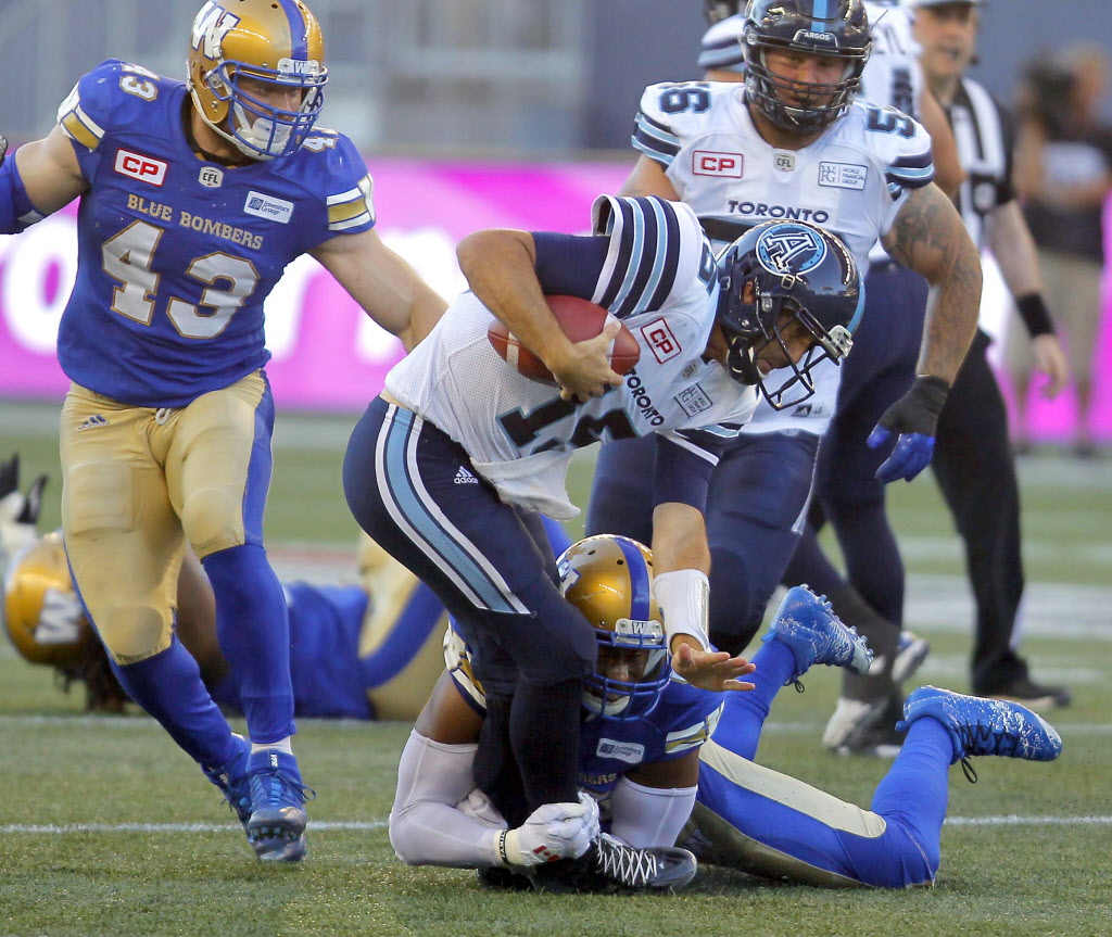 Ricky Ray gets taken down by Bombers Jamaal Westerman with Trent Corney closing in.