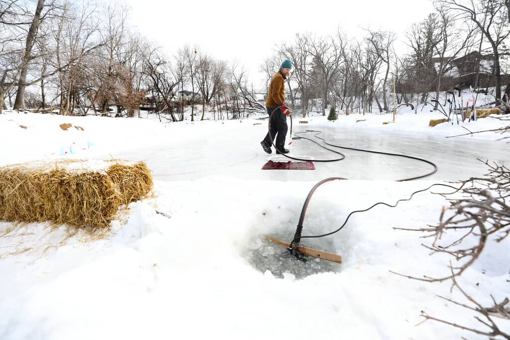 Reder draws water from the Seine River to flood the homemade rink.
