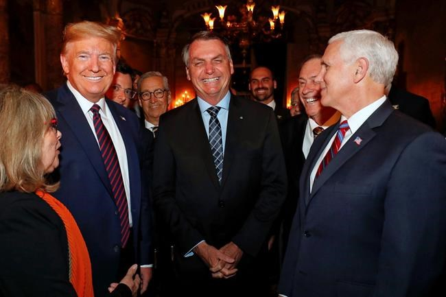 In this March 7, 2020 photo provided by Brazil's presidential press office, Brazil's President Jair Bolsonaro, center, stands with President Donald Trump, second from left, Vice President Mike Pence, right, and Brazil's Communications Director Fabio Wajngarten, behind Trump partially covered, during a dinner in Florida. Wajngarten tested positive for the new coronavirus, just days after the trip, according to Bolsonaro's communications office on Thursday, March 12, 2020. (Alan Santos/Brazil's Presidential Press Office via AP)