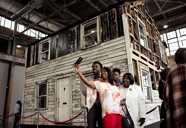 FILE - In this April 1, 2018 file photo, Cheryl Galloway, of Providence, R.I., uses a mobile phone to take a photo with family members in front of the rebuilt house of Rosa Parks at the WaterFire Arts Center in Providence, R.I. The house where Parks sought refuge in Detroit after fleeing the South will be auctioned after being turned into a work of art. Guernsey's auction house says the sale will be held mid-summer and that it's expected to fetch seven figures. (AP Photo/Steven Senne, File)