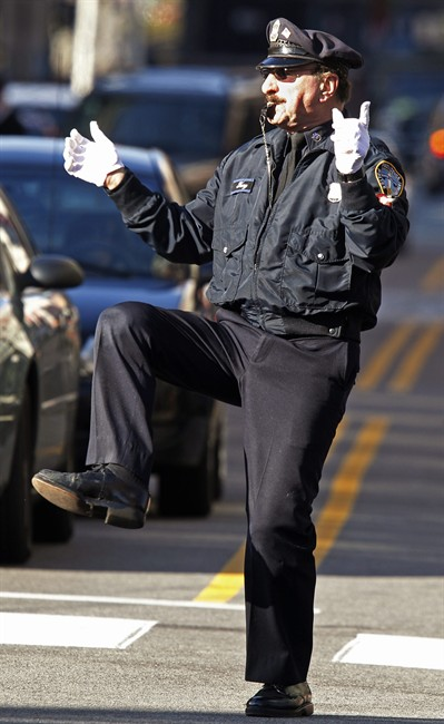 In this Dec. 13, 2012 photo, former Providence Police Department office Tony Lepore directs traffic at an intersection on Dorrance Street in Providence, R.I. Lepore is know as the dancing cop because of his energetic and rhythmic style of moving vehicles and pedestrians through an intersection. (AP Photo/Stephan Savoia)