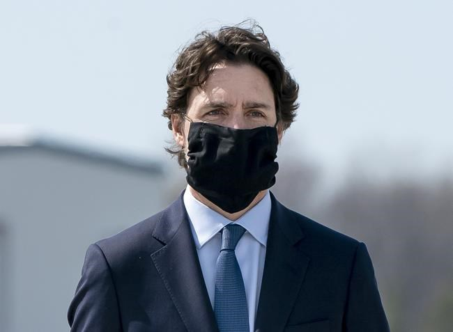 Prime Minister Justin Trudeau wears a mask at a repatriation ceremony for the six Canadian Armed Forces members killed in a helicopter crash off of Greece during Operation Reassurance, at CFB Trenton, Ont. on Wednesday, May 6, 2020. Trudeau says a national recommendation on when and where Canadians should be wearing face masks is coming later today. THE CANADIAN PRESS/Frank Gunn