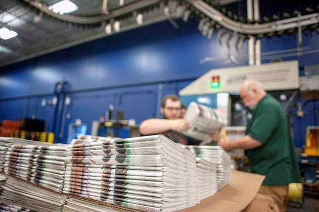 In this April 11, 2018, photo, production workers stack newspapers onto a cart at the Janesville Gazette Printing & Distribution plant in Janesville, Wis. The federal government needs to move quickly to support the Canadian news industry amid the economic downturn brought about by the response to the COVID-19 pandemic, an industry spokesman said Monday. THE CANADIAN PRESS/Angela Major/The Janesville Gazette via AP