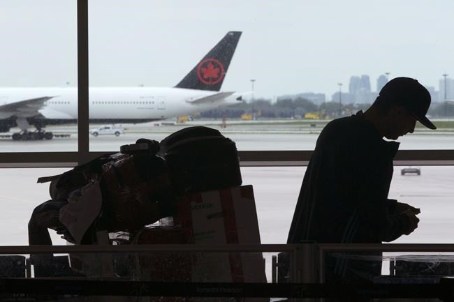 A passenger waits beside his luggage at the departure terminal at Pearson International Airport in Toronto, Friday, May 24, 2019. The federal government says it's extended tight rules on foreign travellers' entering Canada until the end of July, to keep COVID-19 from spreading. THE CANADIAN PRESS/Chris Young