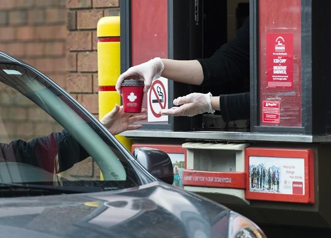 A Tim Hortons employee hands out coffee from a drive-through window to a customer in Mississauga, Ont., on Tuesday, March 17, 2020. Tim Hortons mobile ordering app is being investigating by the Office of the Privacy Commissioner of Canada and provincial agencies in Quebec, B.C. and Alberta.THE CANADIAN PRESS/Nathan Denette