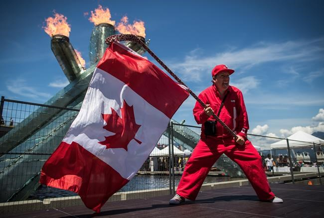 Ricky Johnson waves a Canadian flag on a hockey stick as the Olympic cauldron burns while attending Canada Day celebrations in Vancouver, on Monday July 1, 2019. A different kind of Canada Day is dawning this morning, with large celebrations in many parts of the country replaced with backyard barbecues and digital events. THE CANADIAN PRESS/Darryl Dyck