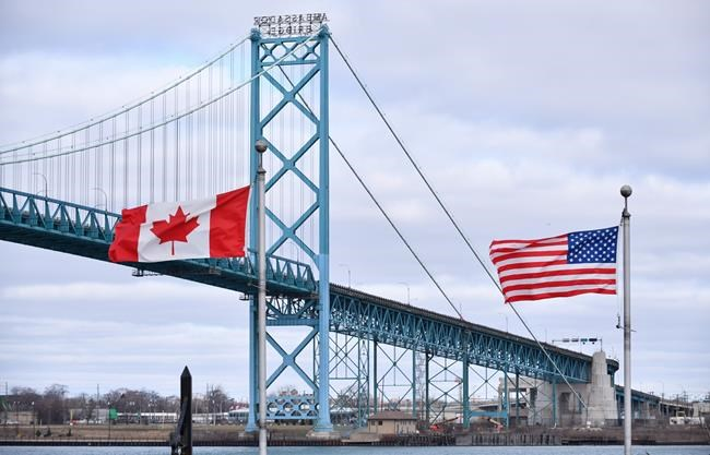 Canadian and American flags fly near the Ambassador Bridge at the Canada-USA border crossing in Windsor, Ont. on Saturday, March 21, 2020. Unique challenges are facing residents in Canadian and U.S. border cities and towns amid a ban on non-essential travel between the two countries during the pandemic. THE CANADIAN PRESS/Rob Gurdebeke