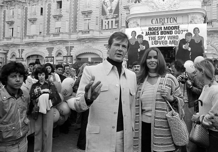 Roger Moore is accompanied by co-star Barbara Bach as they arrive for the screening of their 1977 Bond feature, The Spy Who Loved Me, during the Cannes Film Festival at the French Riviera. Moore played Bond in seven films, more than any other actor.  (CP)