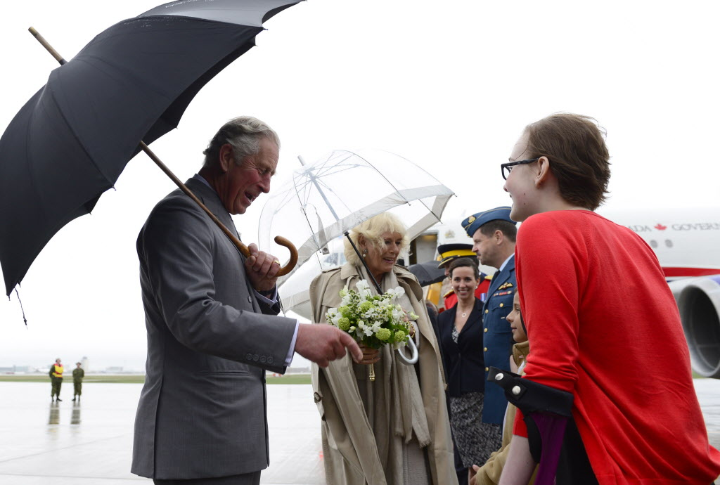 Prince Charles and his wife Camilla are greeted at the airport on a rainy windy day as they arrive in Winnipeg on Tuesday.