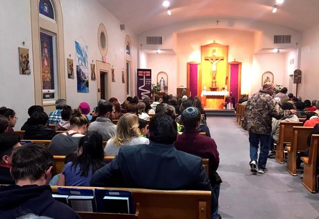 People gather for a vigil at St. Joseph Church in Aztec, N.M., Thursday, Dec. 7, 2017, Students hid in their classrooms, some behind locked doors or in closets, as a gunman opened fire Thursday inside a New Mexico high school, (AP Photo/Russell Contreras)