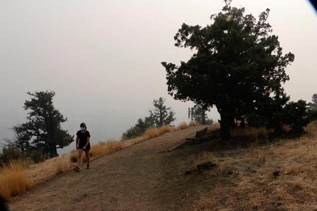 A woman walks up a trail on Pilot Butte, a lava dome overlooking the city of Bend, Ore., Tuesday, Sept. 15, 2020. Wildfires have created hazardous air quality in Bend and other cities across the U.S. West. (AP Photo/Rachel La Corte)