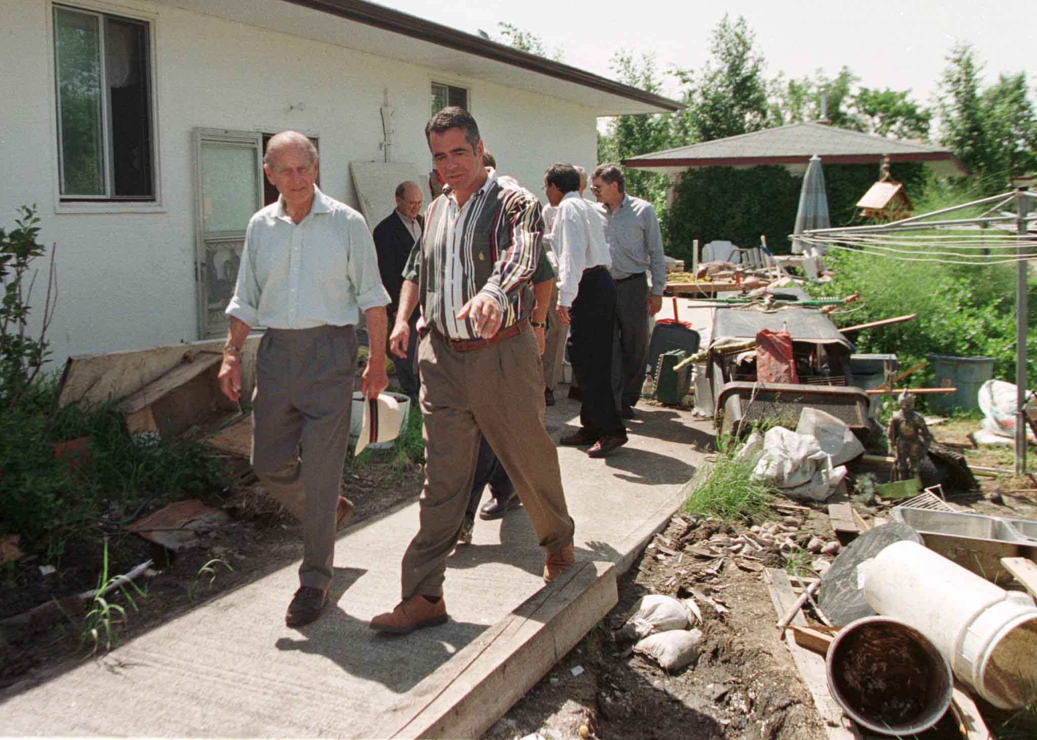 Prince Philip (left) surveys damage in the backyard of a home damaged by flooding of the Red River in 1997.
