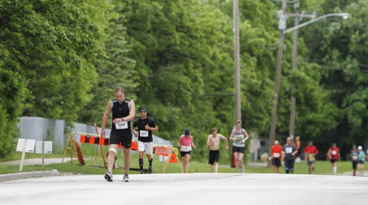 An injured runner (left) pushes through the pain at Mile 24 on River Road in Winnipeg Sunday.