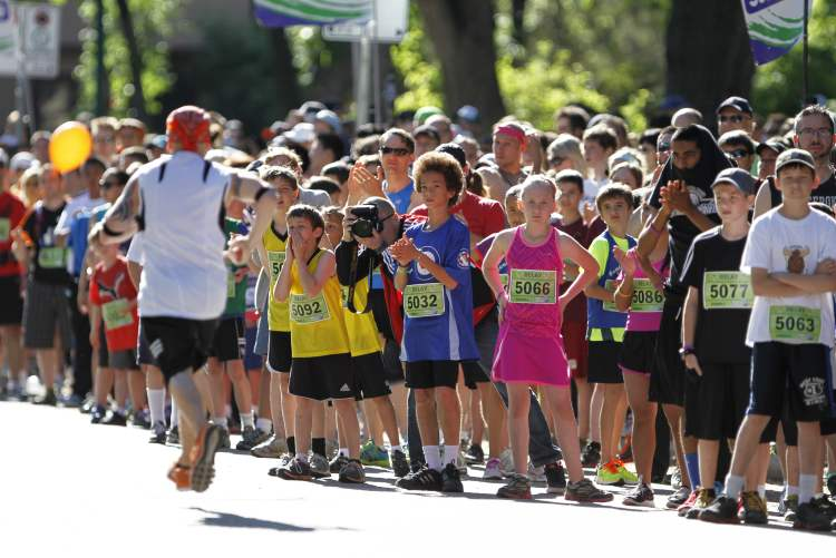 Runners are greeted by a colourful crowd in front of Laura Secord School in Wolseley during the Manitoba Marathon Sunday. (Jessica Burtnick / Winnipeg Free Press)