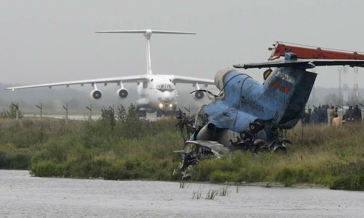 The tail section of the Yak-42 jet that crashed is seen in the foreground as a plane lands at the airport near Yaroslavl Russia on Friday, Sept. 9, 2011. The team had been heading to Minsk, Belarus to play its opening game of the Kontinental Hockey League season.