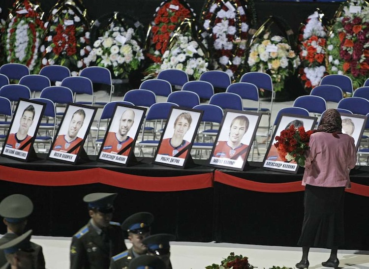 A woman grieves in front of a lineup of player photographs at the memorial service in Arena Yaroslavl for the victims of the plane crash. The team had been heading to Minsk, Belarus to play its opening game of the Kontinental Hockey League season. (Misha Japaridze / The Associated Press archive)