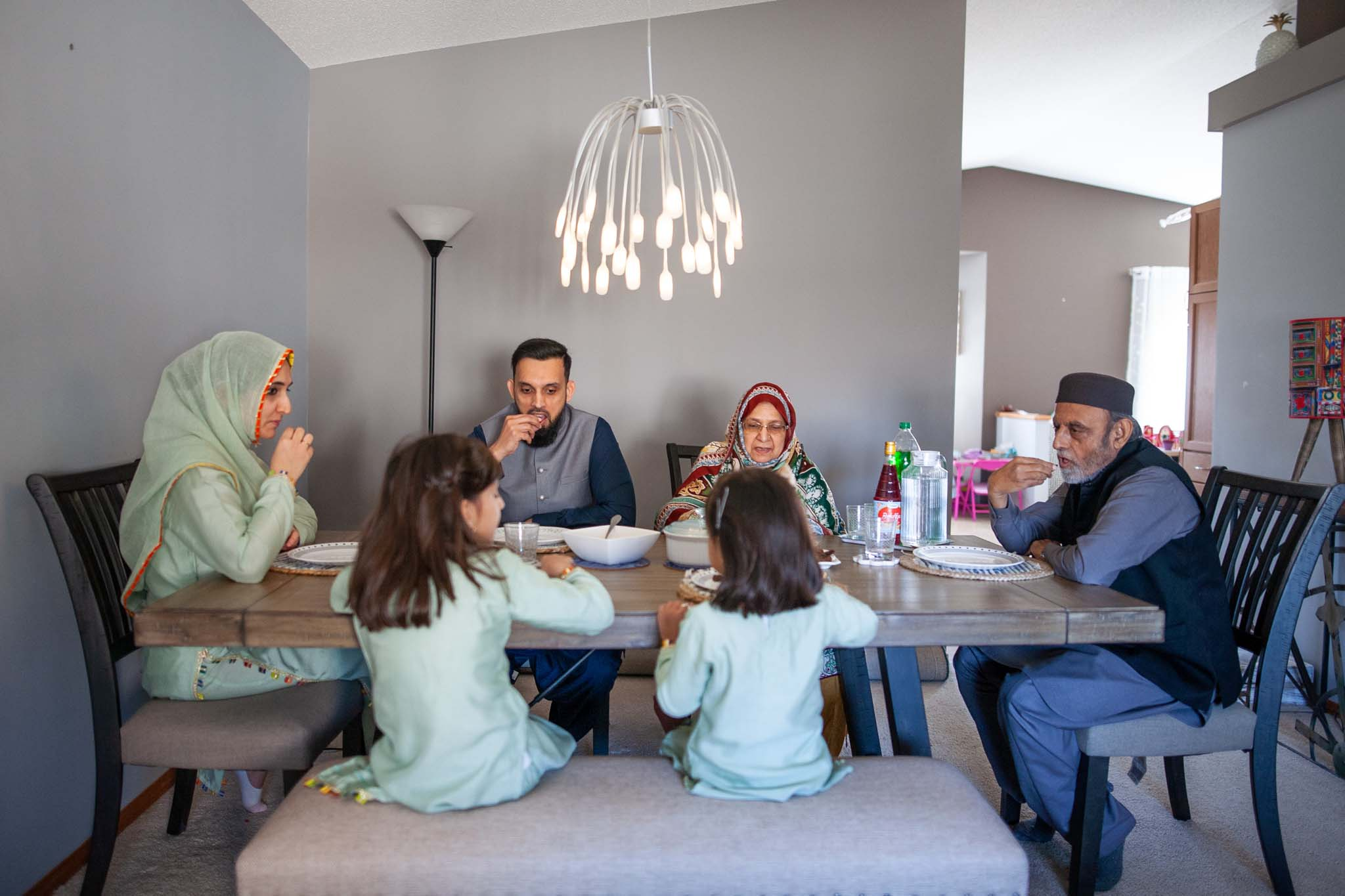 Asra  Waleed's family, including grandparents who also live in the home, sit around a table as they demonstrate breaking the ramadan fast.