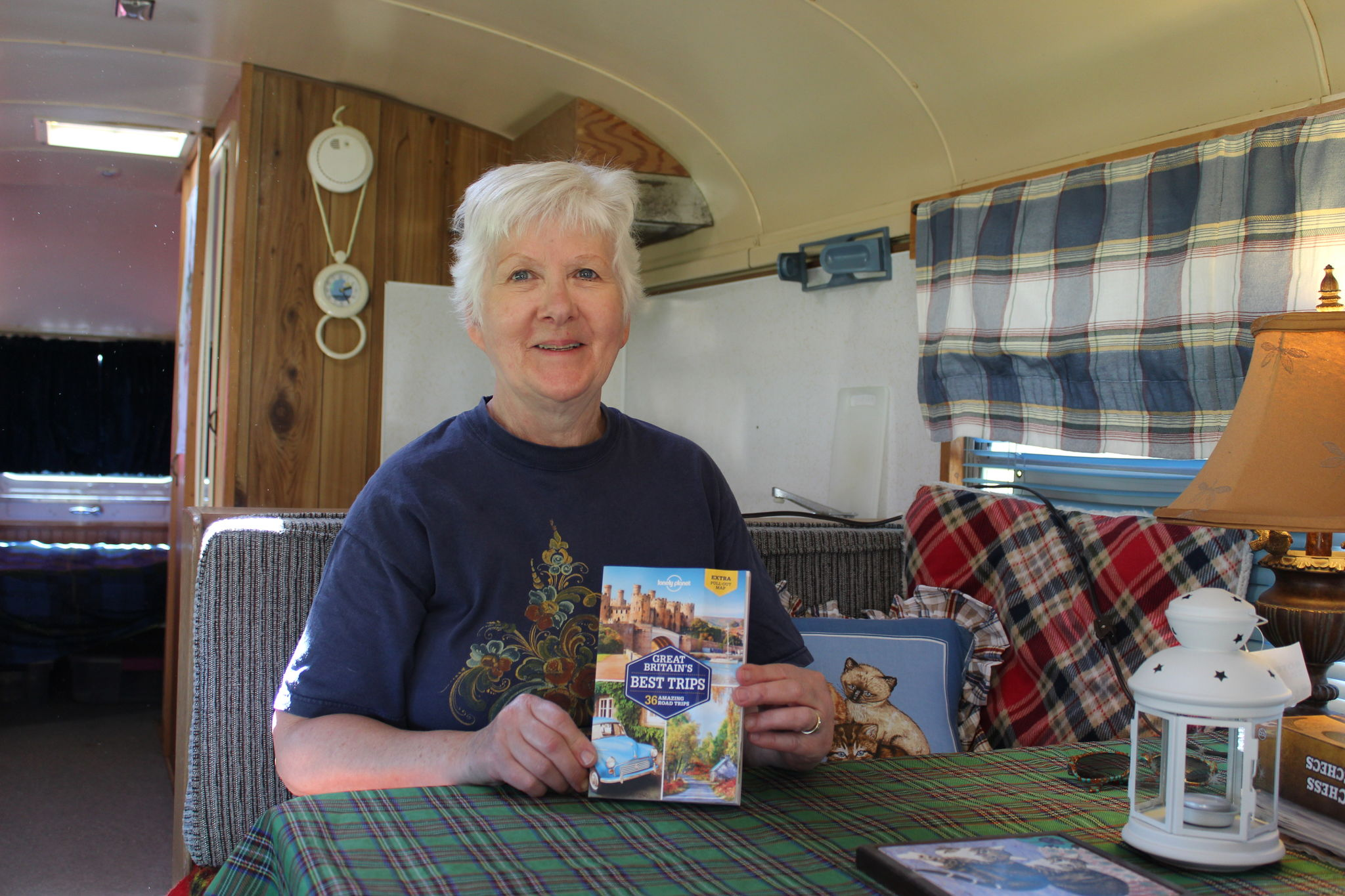 Margaret Feilberg displays a copy of a favourite Great Britain travel guide that inspired the Scottish theme of a cabin fashioned from a converted school bus. Bill Stevenson's family tartan adorns the dining table.