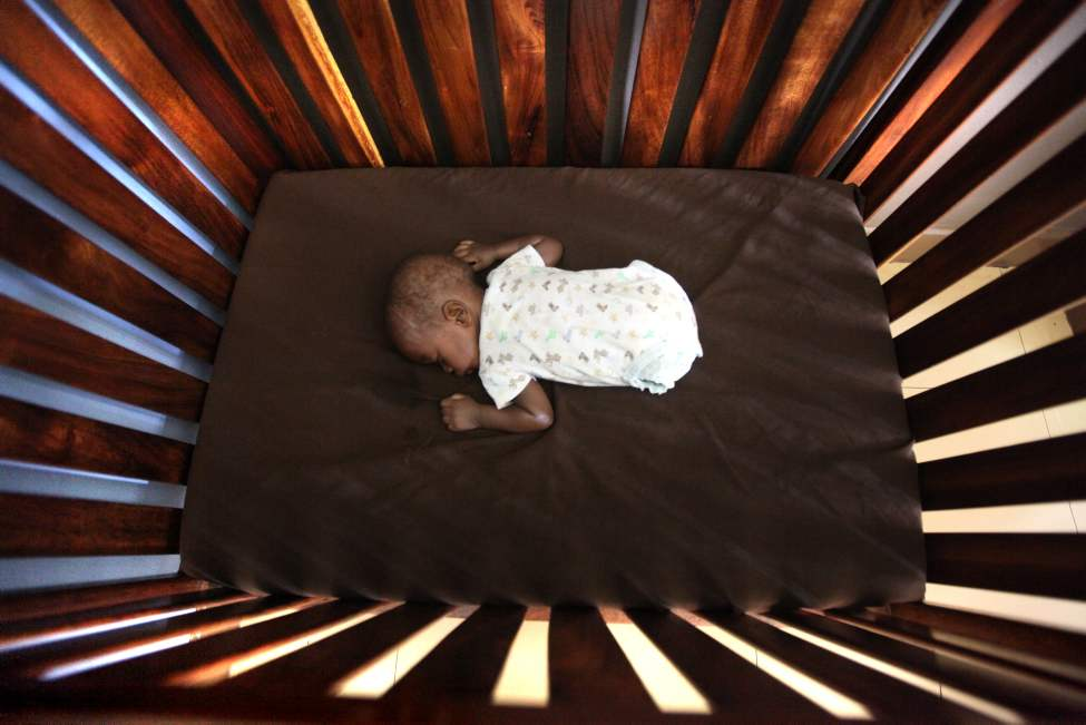 Four-month-old Jonah who was born with no legs has a afternoon nap in his crib at Bulrushes, a home for high risk, abandoned and orphaned babies in Kampala's city centre in Uganda. 