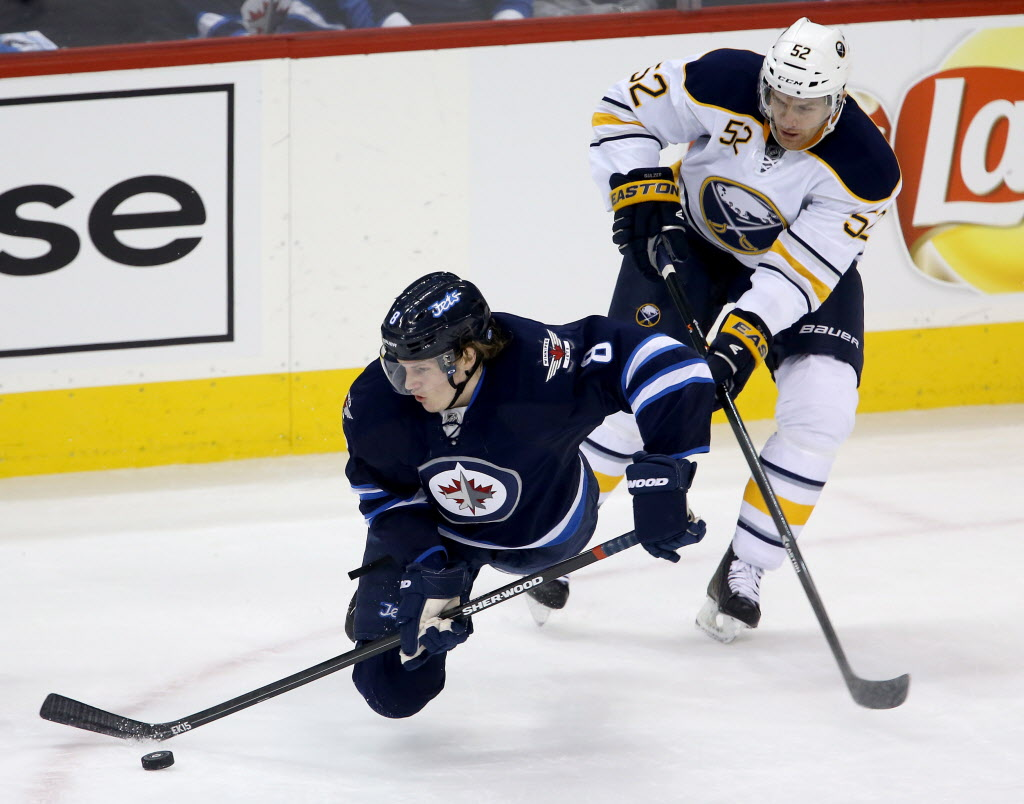 Winnipeg Jets' Jacob Trouba (#8) is tripped up by Buffalo Sabres' Alexander Sulzer (#52) during the first period in Winnipeg Tuesday.  (Trevor Hagan / The Canadian Press)