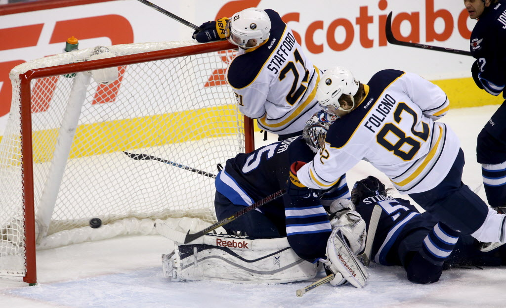 Buffalo Sabres' Marcus Foligno (#82) scores a goal on Winnipeg Jets' goaltender Al Montoya (#35) as Sabres' Drew Stafford (#21) knocks the net off the mooring. The first-period goal was disallowed on the ice and the review was inconclusive.