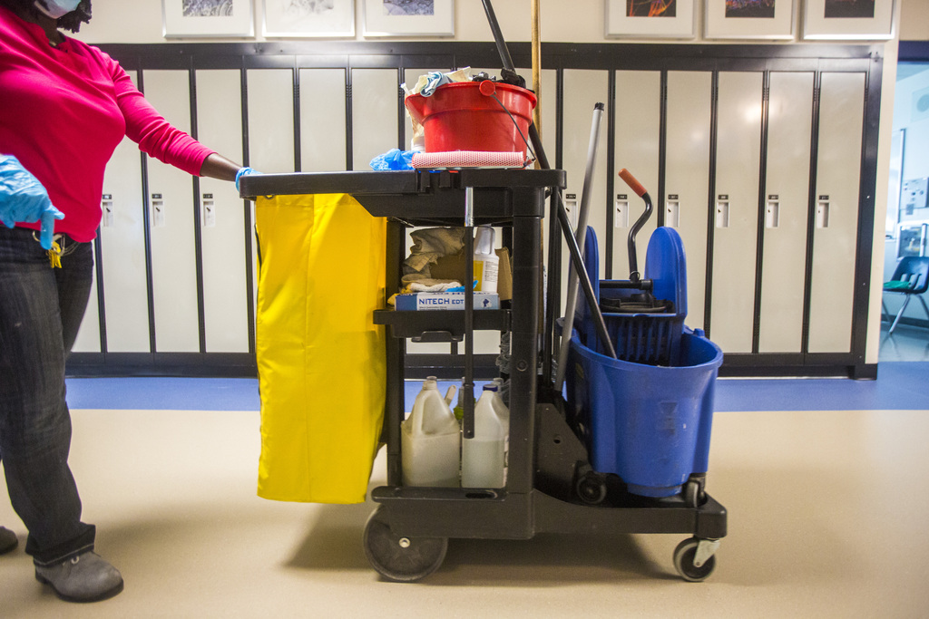 Deborah Boateng, a cleaner at Churchill High School, with her cart stocked with bottles of disinfectant, cloth wipes and a mop bucket.