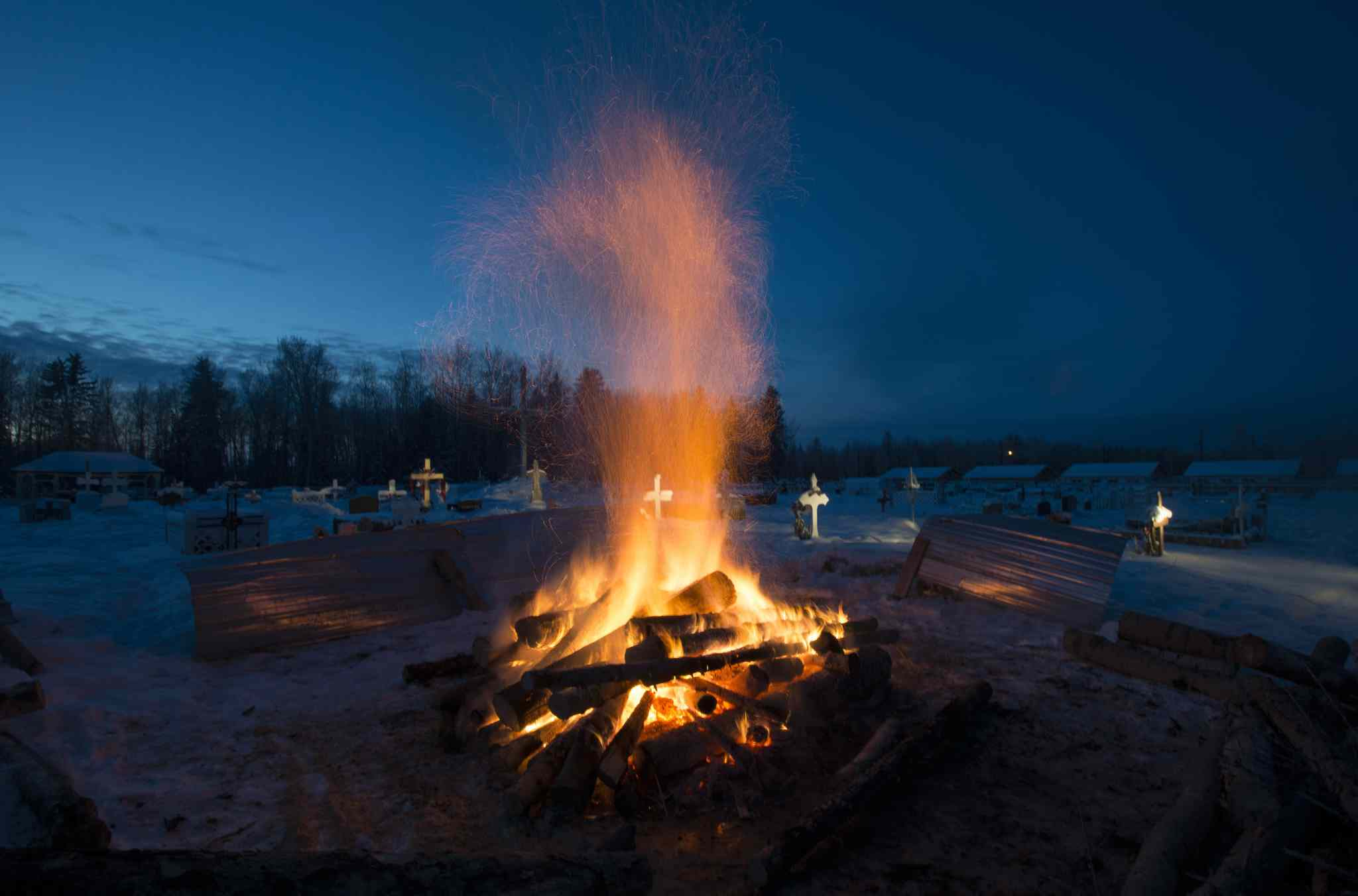 A fire burns as it thaws the frozen cemetery ground in order to dig a grave for one of the shooting victims.