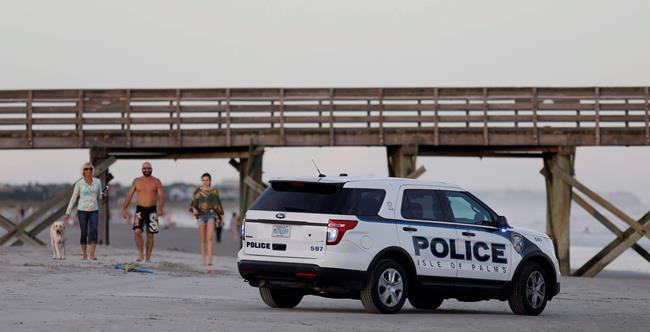 A police car makes a presence on the beach at sunset on the Isle of Palms, S.C., as Hurricane Florence slightly weakens in the Atlantic ocean Wednesday, Sept. 12, 2018. The National Hurricane Center said Wednesday evening that the storm is expected to bring life-threatening storm surge and rainfall to the Carolinas as it approaches the coast Thursday and Friday. (AP Photo/Mic Smith)