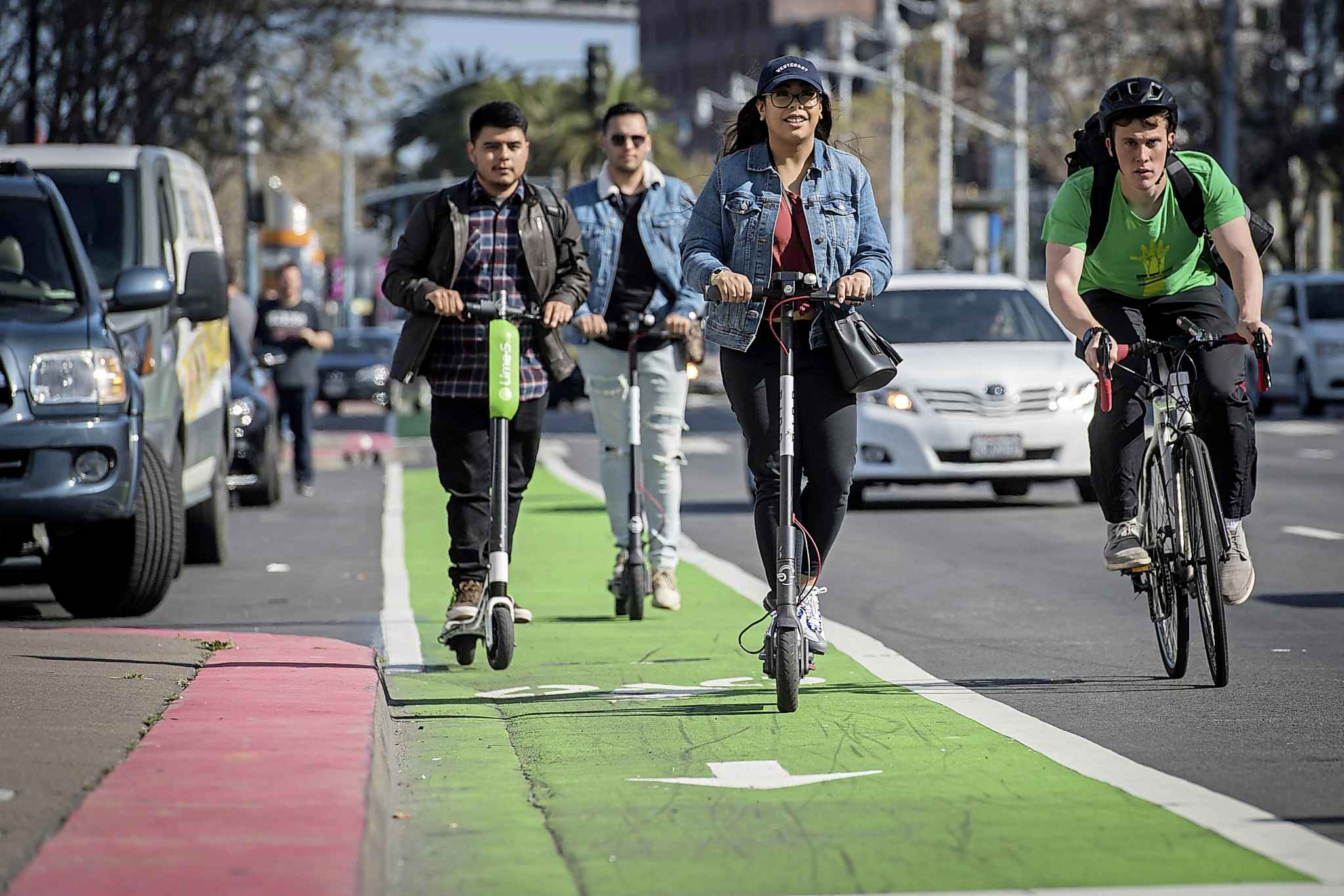 People ride LimeBike and Bird Rides shared electric scooters in San Francisco. (Bloomberg photo by David Paul Morris)