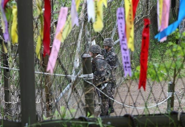 South Korean army soldiers look toward North's side as ribbons hanging on a wire fence wishing for the reunification of the two Koreas at the Imjingak Pavilion in Paju near the border village of Panmunjom, South Korea, Wednesday, May 16, 2018. North Korea on Wednesday canceled a high-level meeting with South Korea and threatened to scrap a historic summit next month between U.S. President Donald Trump and North Korean leader Kim Jong Un over military exercises between Seoul and Washington that Pyongyang has long claimed are invasion rehearsals. (AP Photo/Ahn Young-joon)