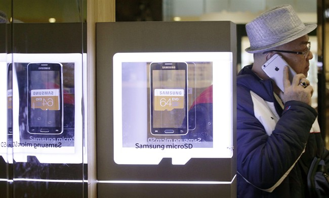 A man uses an Apple iPhone near the advertisement of Samsung Electronics' micro SD cards at a Samsung shop in Seoul, South Korea Thursday, Jan. 29, 2015. Samsung lost the battle of the big phones last quarter as Apple's copycat large iPhone lured buyers in the crucial Chinese market. The South Korean company said Thursday its profit sank last quarter, with an improvement in its semiconductor business insufficient to mask its mobile problems. (AP Photo/Ahn Young-joon)