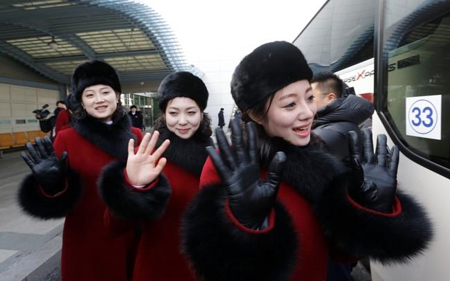 North Korean cheering squads wave upon their arrival at the Korean-transit office near the Demilitarized Zone in Paju, South Korea, Wednesday, Feb. 7, 2018. A North Korean delegation, including members of a state-trained cheering group, arrived in South Korea on Wednesday for the Pyeongchang Winter Olympics. (AP Photo/Ahn Young-joon. Pool)