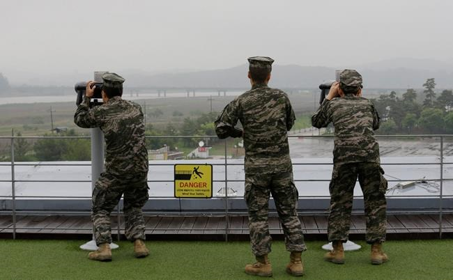 South Korean marine force members look toward North's side through binoculars at the Imjingak Pavilion in Paju near the border village of Panmunjom, South Korea, Wednesday, May 16, 2018. North Korea on Wednesday canceled a high-level meeting with South Korea and threatened to scrap a historic summit next month between U.S. President Donald Trump and North Korean leader Kim Jong Un over military exercises between Seoul and Washington that Pyongyang has long claimed are invasion rehearsals. (AP Photo/Ahn Young-joon)