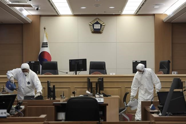 Workers wearing protective gears spray disinfectant as a precaution against the new coronavirus at Gwangju District Court in Gwangju, South Korea, Tuesday, Feb. 25, 2020. China and South Korea on Tuesday reported more cases of a new viral illness that has been concentrated in North Asia but is causing global worry as clusters grow in the Middle East and Europe. (Park Chul-hong/Yonhap via AP)