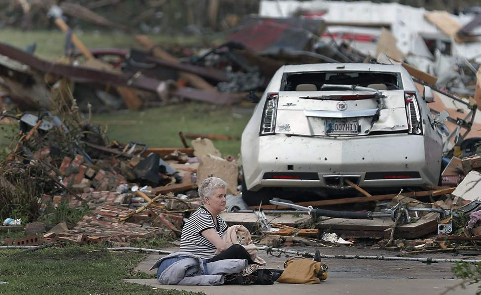 Kay James holds her cat as she sits in her driveway after her home was destroyed by the tornado that hit the area near 149th and Drexel on Monday in Oklahoma City, Okla.  (Chris Landsberger / The Oklahoman)