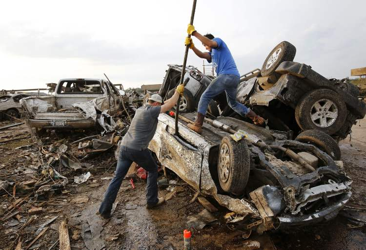 Two men attempt to pry open a door on this car to check for victims in a business parking lot west of I-35 south of 4th Street in Moore, on Monday, May 20, 2013. (AP Photo/The Oklahoman, Jim Beckel)