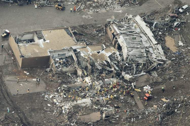 This aerial photo shows the remains of homes hit by a massive tornado in Moore, Okla., Monday May 20, 2013. (AP Photo/Steve Gooch)