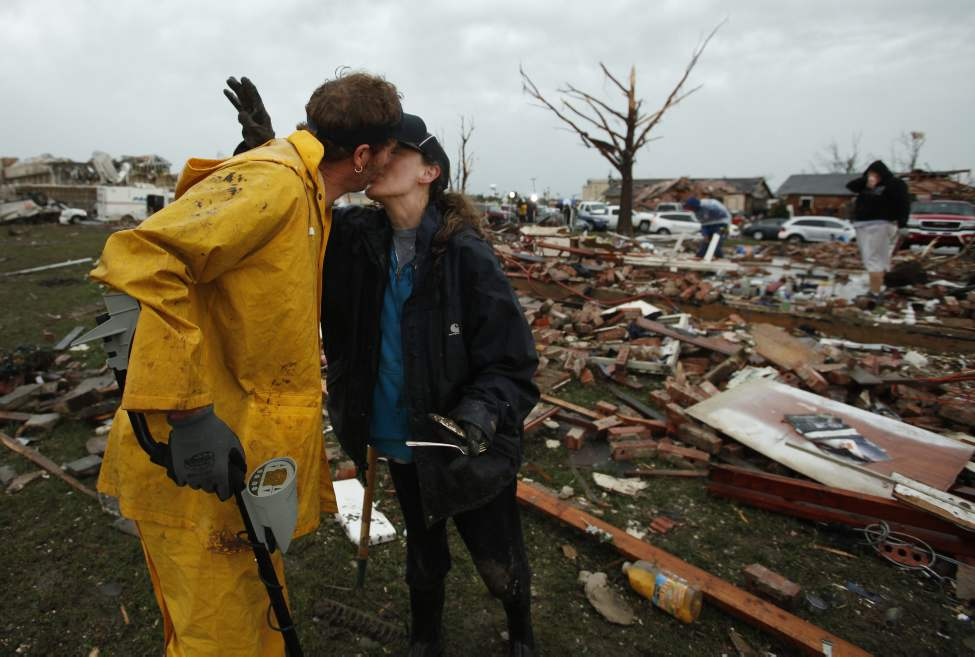 Ann Friess kisses her husband, Dan, for finding part of her grandmother's silver while looking for personal items among the remains of their home along SW 6th Street in Moore, Okla., on Tuesday.