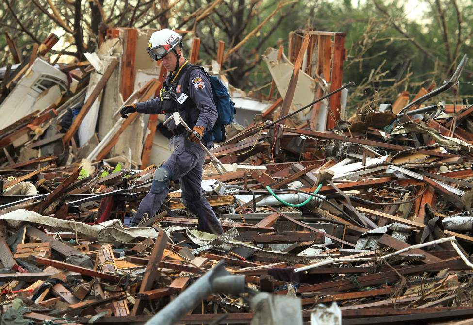 A member of Nebraska Task Force-1 walks through the debris of a home along SW 6th Street in Moore, Okla., on Tuesday. (Brad Loper / The Dallas Morning News)
