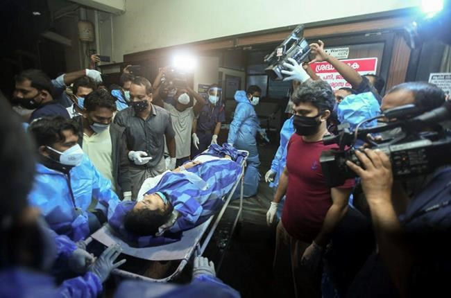 One of the persons injured after an Air India Express flight skidded off a runway while landing at the Kozhikode airport is brought for treatment to the Medical College Hospital in Kozhikode, Kerala state, India, Friday, Aug. 7, 2020. (AP Photo)