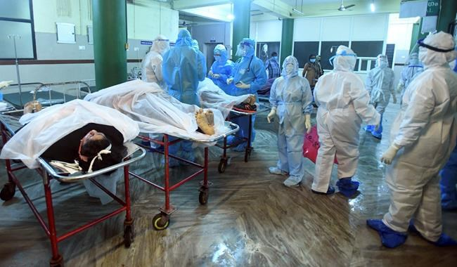 Medical personnel in personal protective wear stand next to bodies of victims after an Air India Express flight skidded off a runway while landing at the Kozhikode airport iare attended to at the Medical College Hospital in Kozhikode, Kerala state, India, Friday, Aug. 7, 2020. (AP Photo/Shijith Sreedhar)