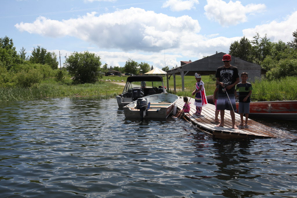 Young residents of Shoal Lake 40 First Nation gather on the main dock to their man-made island to fish Wednesday during a special event marking the 100th anniversary for the flooding of their land to provide water for the City of Winnipeg.