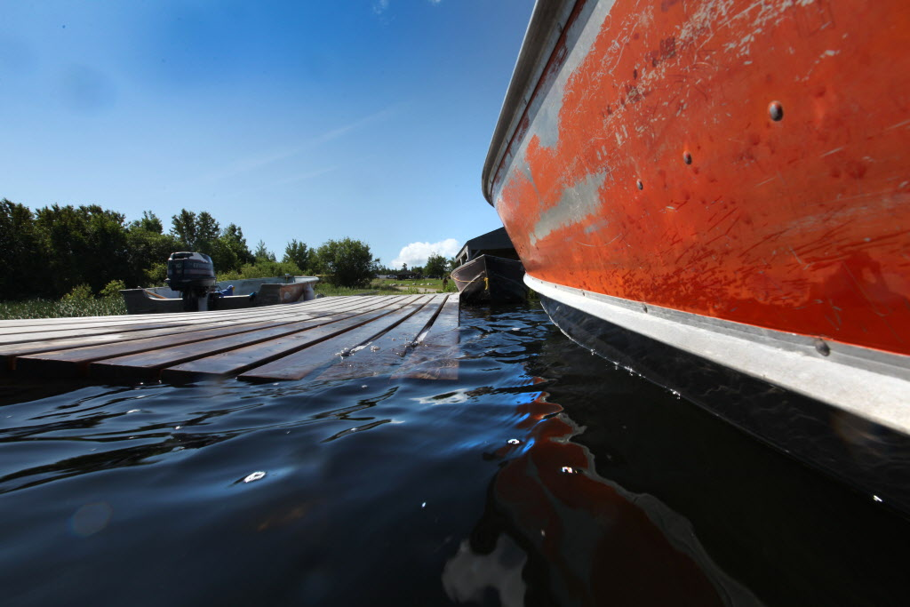 A fishing boat arrives at the docks of Shoal Lake 40 First Nation Wednesday, bringing government officials and dignitaries to a man-made island for the 100th anniversary event. (Ruth Bonneville / Winnipeg Free Press)