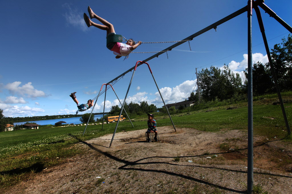 Children play on a set of swings near the docks of Shoal Lake 40 First Nation Wednesday just before government officials and dignitaries arrive on their man-made island to mark the 100th anniversary for the flooding of their land to provide water for the City of Winnipeg.