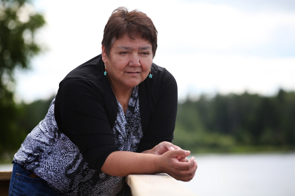 Linda Redsky, a resident of Shoal Lake 40 First Nation, looks into the clear water at the edge of her home where she went through the ice and almost drowned while fetching water in the winter. The community held  an event Wednesday marking the 100th anniversary of the flooding of their land to provide water for the City of Winnipeg.