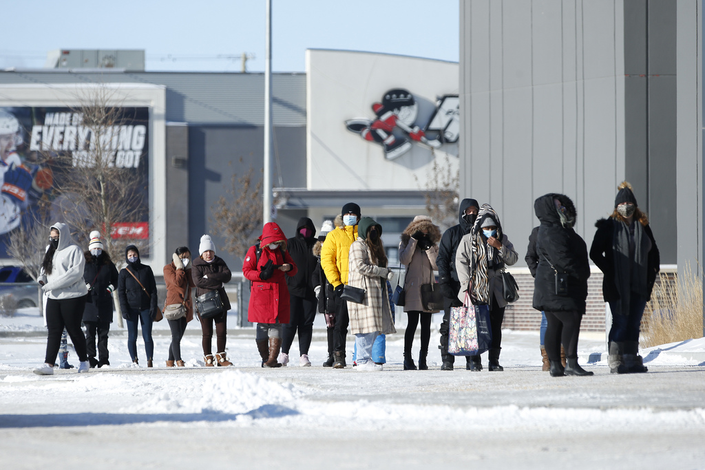 Shoppers wait in line outside Homesense and Winners Sunday.